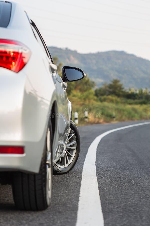 Achterkant van nieuw zilveren autoparkeren op de asfaltweg stock fotografie