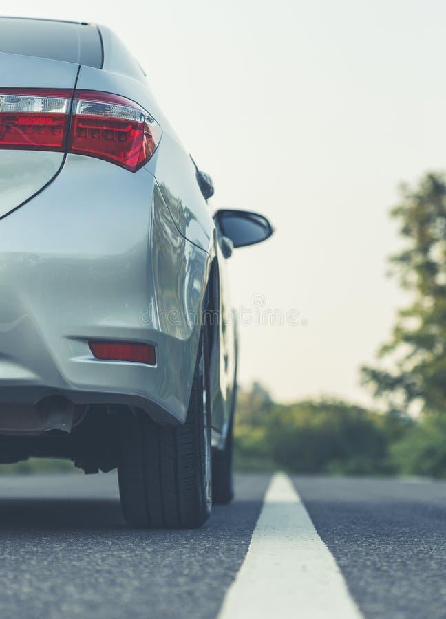 Achterkant van nieuw zilveren autoparkeren op de asfaltweg stock afbeeldingen