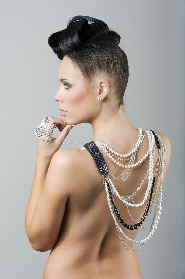 Achterkantvrouw met kapsel en juwelen stock foto's
