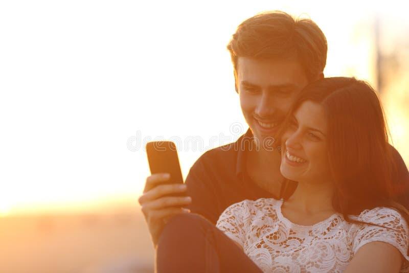 Achterlicht van een paar die een slimme telefoon delen stock fotografie
