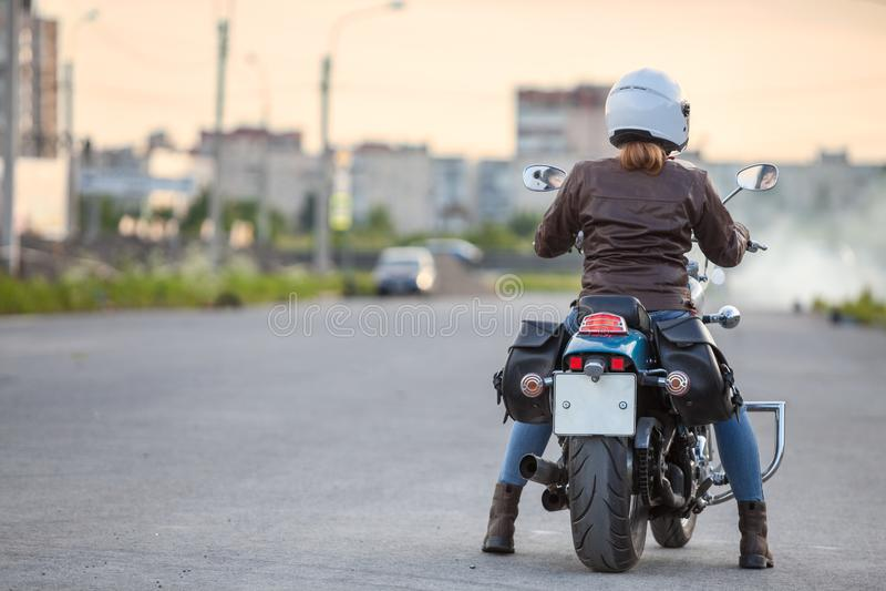 Achtermening bij jonge vrouwenmotorrijder klaar aan stard die op motorfiets op asfaltweg berijden, exemplaarruimte stock foto's
