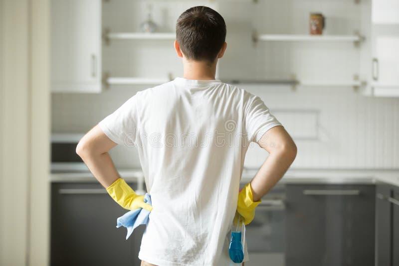 Achtermening bij mensenhanden bij zijn heupen, die keuken waarnemen stock fotografie