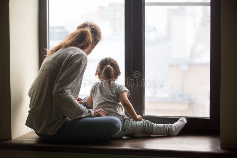 Achtermening bij van de jong geitjedochter en moeder zitting op vensterbank royalty-vrije stock foto
