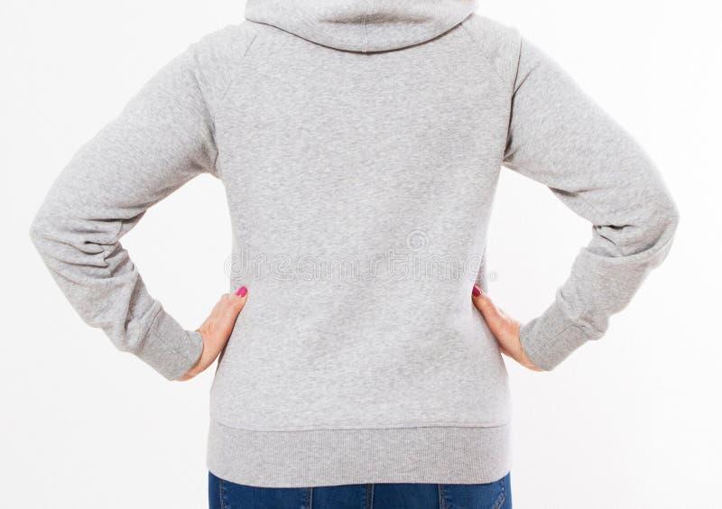 Achtermening: de mooie Europese medio oude vrouw kleedde zich in een lichtgrijs toevallig jasje met een kap die - studio voor een stock foto's