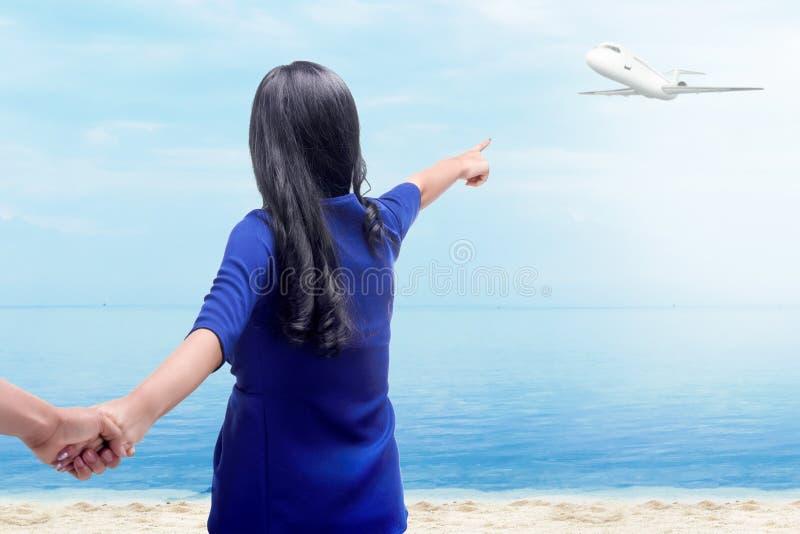 Achtermening die van Aziatische vrouw haar vriendhanden op het strand houden stock afbeelding