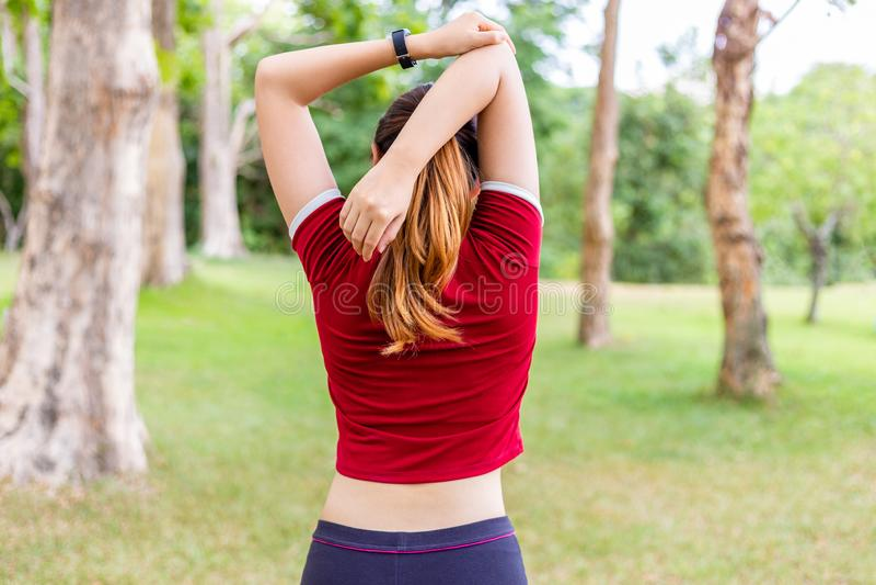 Achtermening die van jonge atletenvrouw haar hoger wapen bicep before and after haar ochtendoefening uitrekken bij een openbaar p royalty-vrije stock afbeeldingen