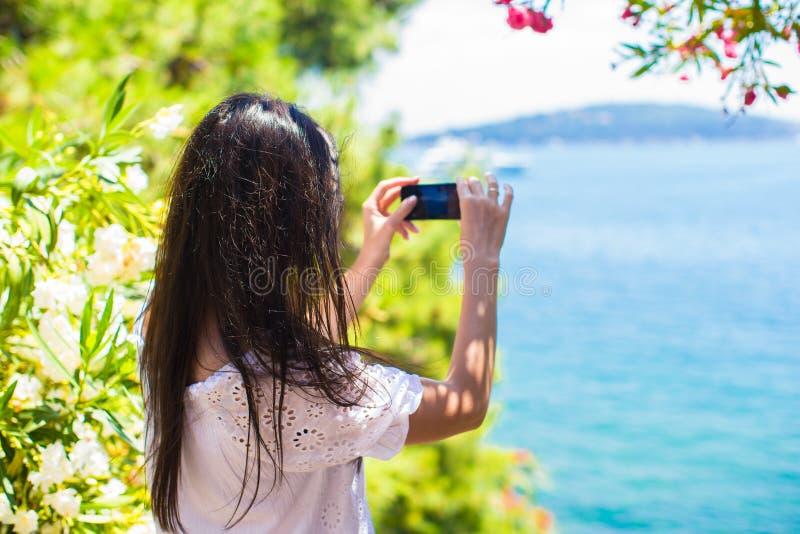 Achtermening die van jonge vrouw foto met telefoon nemen stock foto's