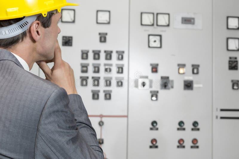 Achtermening die van mannelijke supervisor controlekamer in de industrie onderzoeken stock afbeeldingen