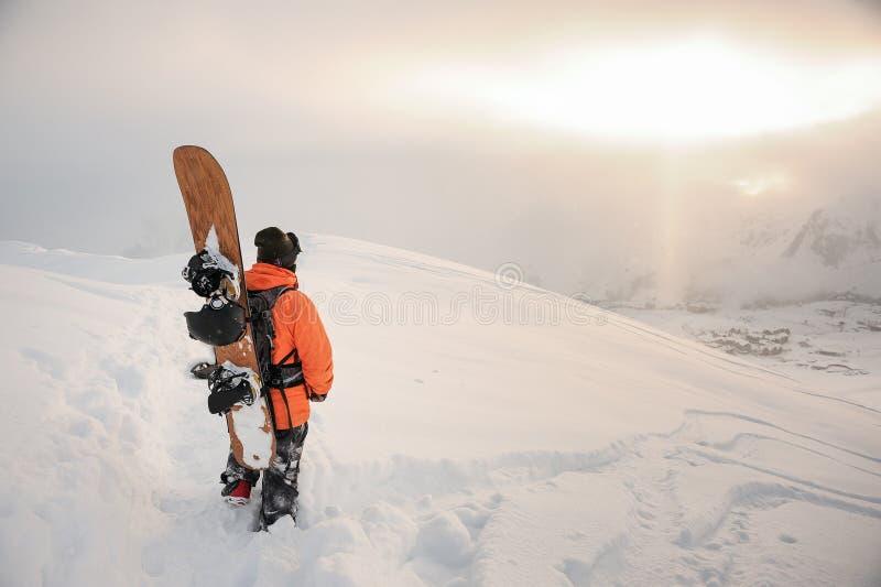 Achtermening die van professionele snowboarder zich op de berg p bevinden stock afbeelding