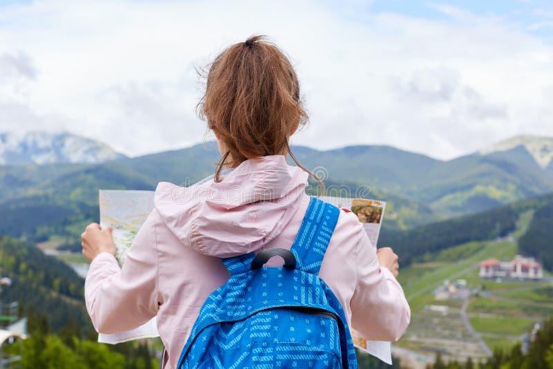 Achtermening die van reis zich boven de kaart van de heuvelholding met huidige route bevinden zich te bewegen, prachtig berglands stock afbeeldingen