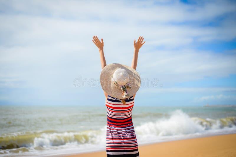Achtermening die van romantische dame die de zomer van strand en zon geniet, op zee golft stock foto