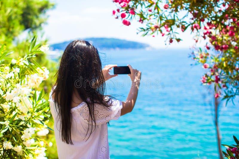 Achtermening die van toeristenvrouw foto met telefoon nemen royalty-vrije stock foto's