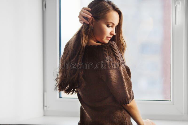 Achtermening die van vrouw dichtbij venster en zich wat betreft haar bevinden stock fotografie
