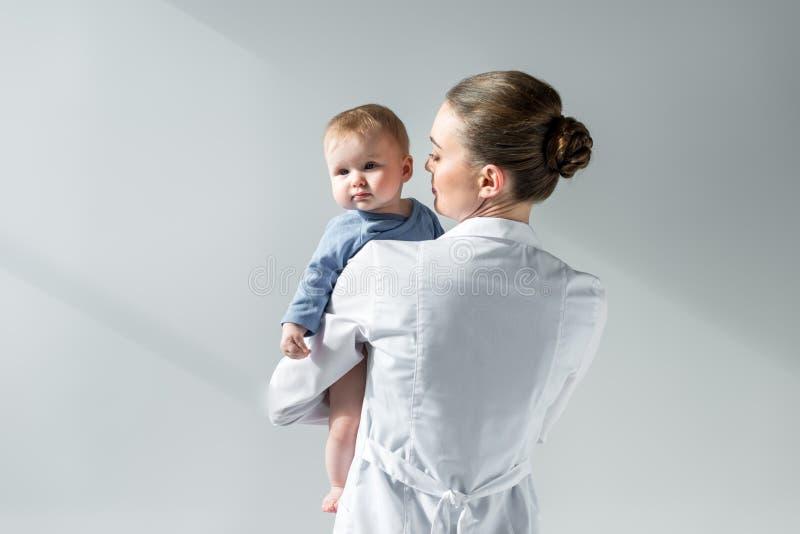 achtermening die van vrouwelijke pediater weinig baby houden stock afbeelding