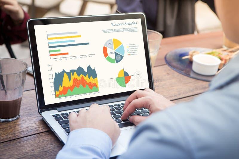 Achtermening die van zakenman die laptop met behulp van die statistiekengegevens over laptop het scherm analyseren, met grafieken stock fotografie