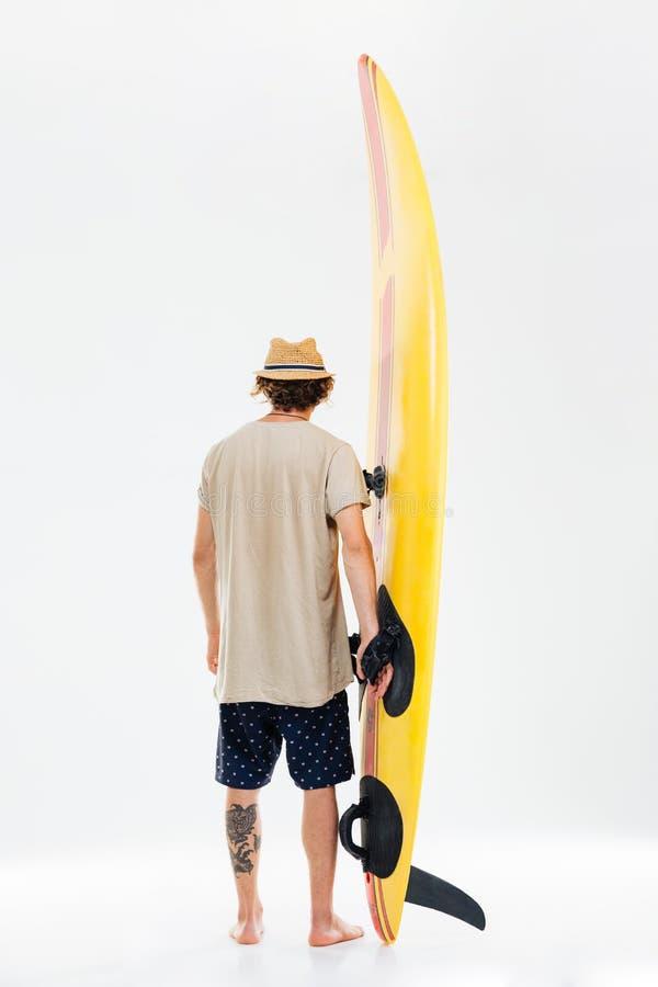 Achtermening een jonge surfplank van de surferholding royalty-vrije stock afbeeldingen