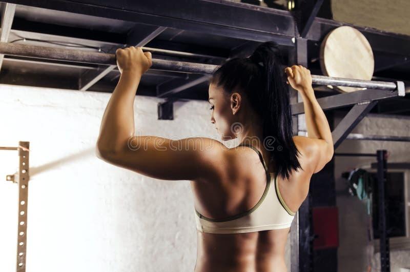 Achtermening, sterke jonge vrouwenbodybuilder stock foto
