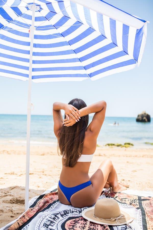 Achtermening van Aantrekkelijke vrouw met het gelooide huid stellen bij strand in zonnige dag Het portret van rug van modieus mei royalty-vrije stock afbeelding