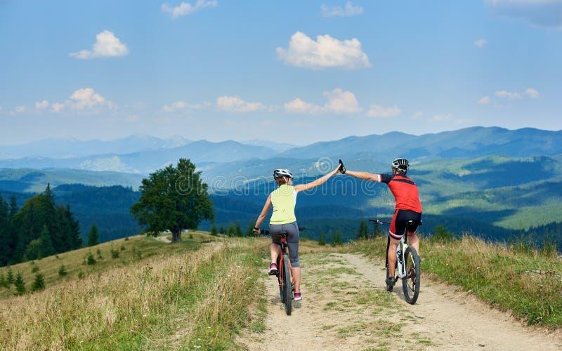 Achtermening van actieve paarfietsers in sportkleding en helmen die onderaan de dwarsfietsen van het land cirkelen royalty-vrije stock fotografie
