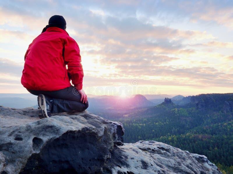 Achtermening van alleen wandelaar in donkerrode openluchtkleren die op rots zitten royalty-vrije stock afbeeldingen