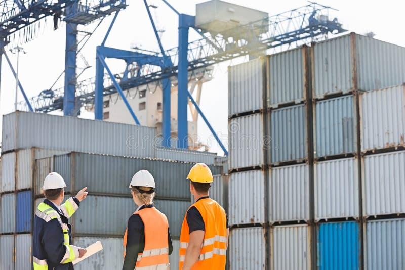 Achtermening van arbeiders die ladingscontainers in het verschepen van werf inspecteren stock afbeelding