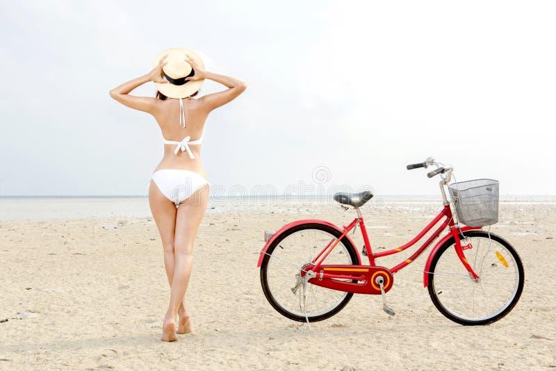 Achtermening van Aziatisch sexy meisje met hoed en bikini met fiets op het strand royalty-vrije stock foto