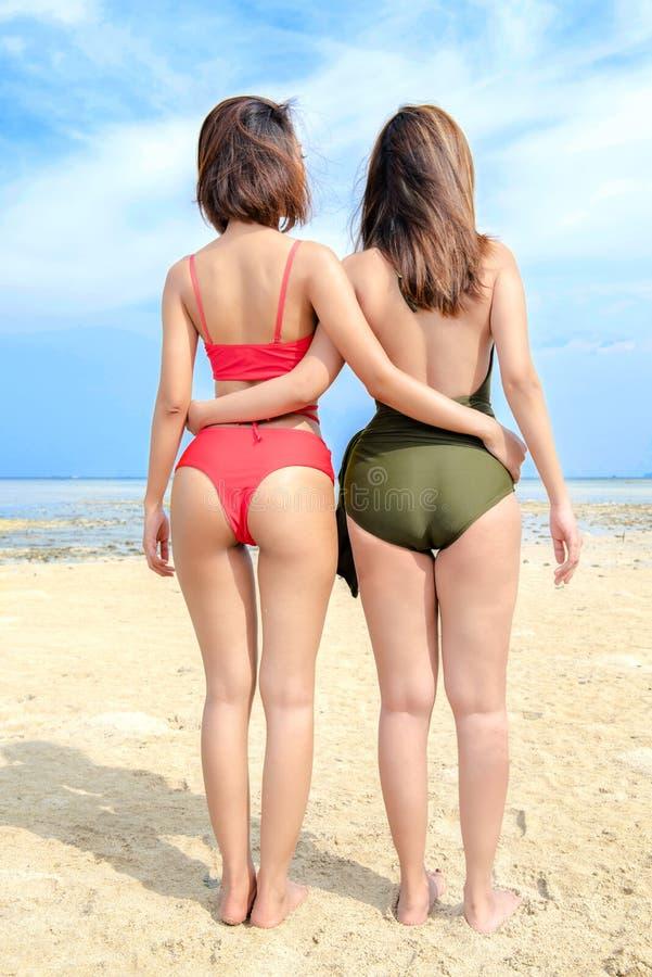 Achtermening van Aziatisch sexy meisje twee in bikini en zwempak op het strand stock fotografie