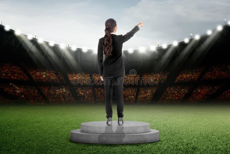 Achtermening van Aziatische bedrijfsvrouw status op podium stock foto