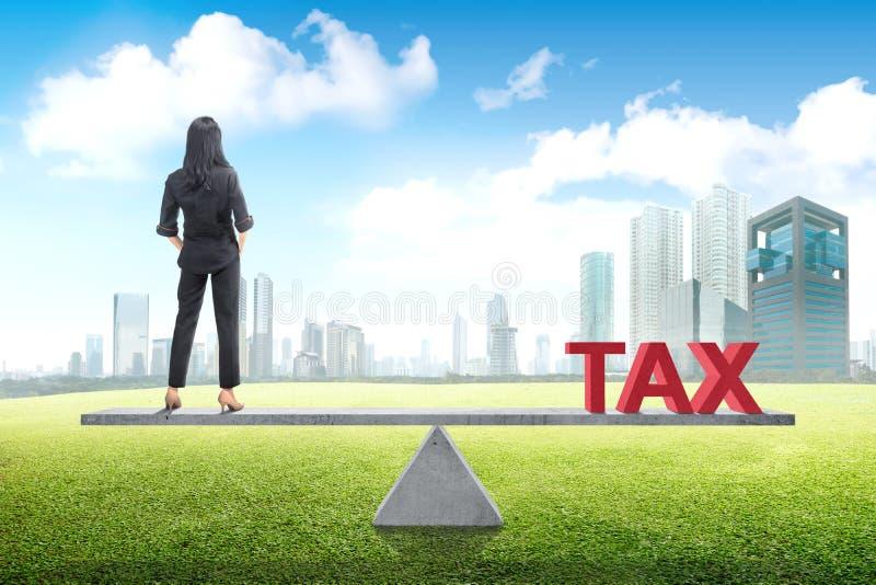 Achtermening van Aziatische bedrijfsvrouwentribune evenwichtig met belasting royalty-vrije stock foto's