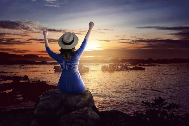 Achtermening van Aziatische vrouw in hoedenzitting op de rots en het bekijken de oceaanmening royalty-vrije stock foto