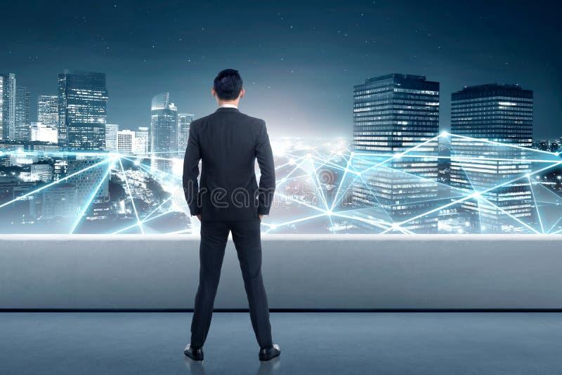Achtermening van Aziatische zakenman die netwerkverbinding bekijken royalty-vrije stock afbeelding