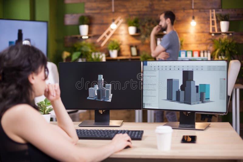 Achtermening van bedrijfsvrouwenzitting op het bureaukantoor die aan haar project werken stock foto