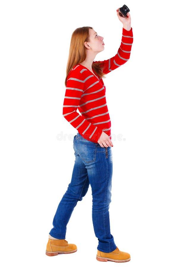 Achtermening van bevindende jonge mooie vrouw en het gebruiken van een camera stock afbeelding
