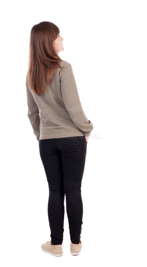 Achtermening van bevindende jonge mooie vrouw in jeans royalty-vrije stock afbeelding