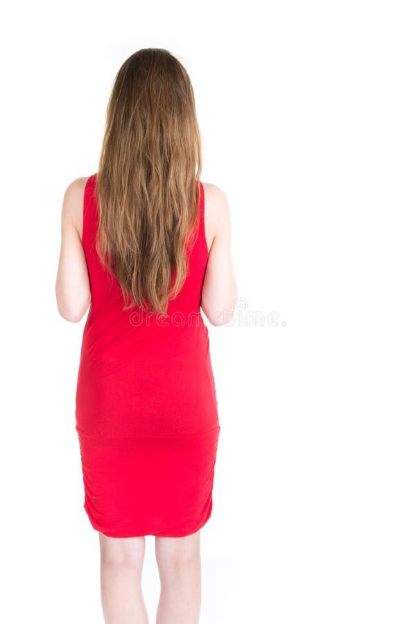 Achtermening van bevindende jonge mooie vrouw in kleding stock fotografie