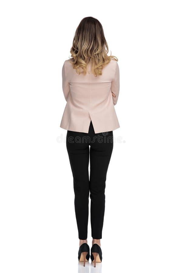 Achtermening van blonde slimme toevallige vrouw in roze kostuum royalty-vrije stock foto's