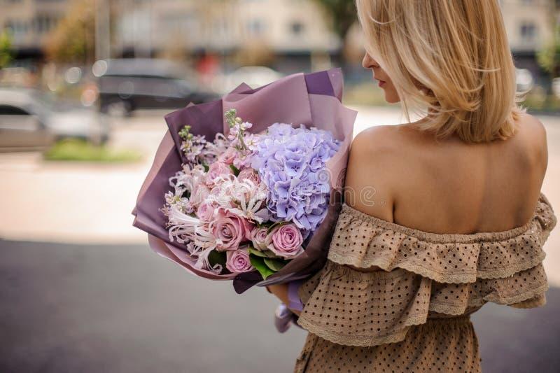 Achtermening van blondevrouw in beige kleding die een romantische bouq houden stock fotografie