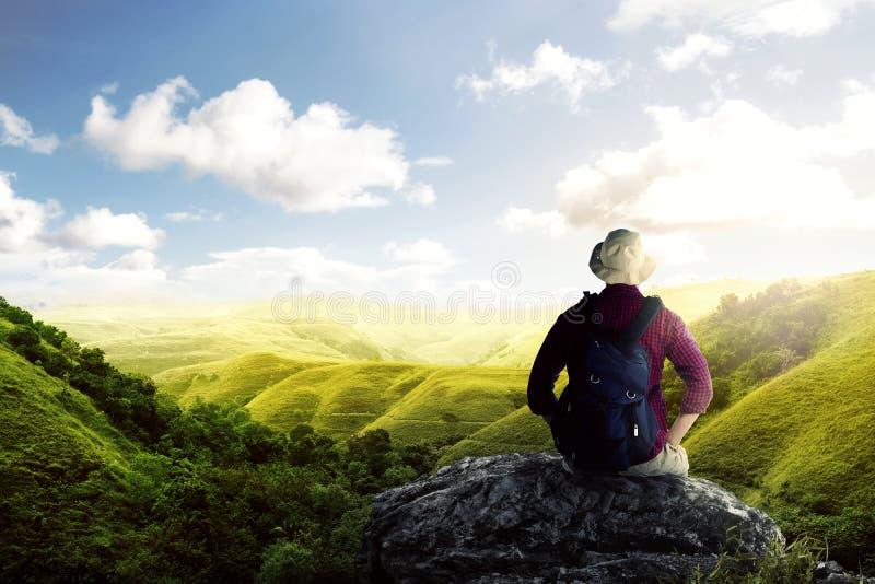 Achtermening van de Aziatische mens in hoed met rugzakzitting op de rots en het bekijken groene meningen royalty-vrije stock afbeeldingen