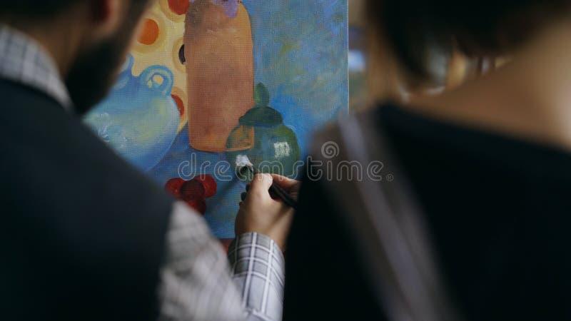 Achtermening van de Bekwame kunstenaarsmens die en jong meisje de grondbeginselen van het schilderen in kunststudio onderwijzen t stock foto