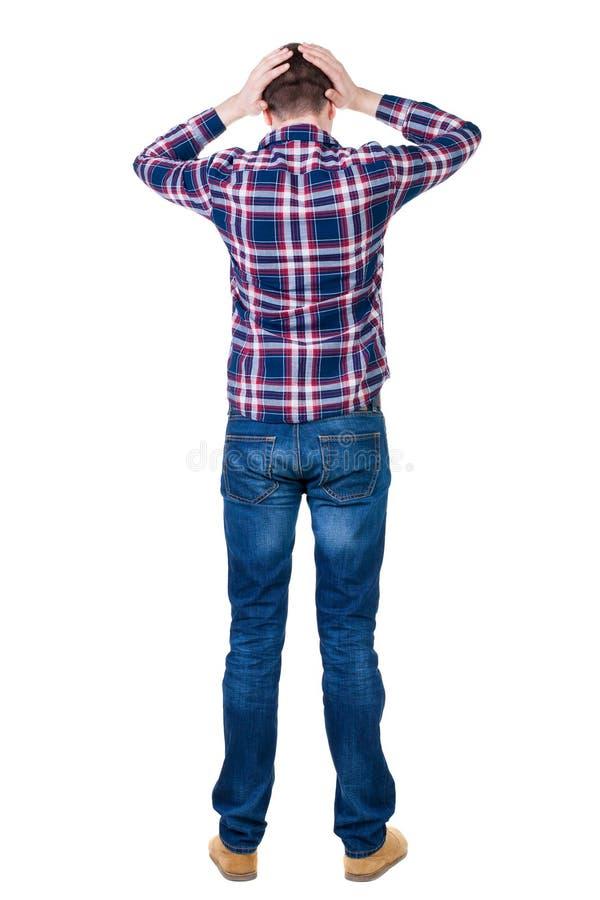 Achtermening van de boze jonge mens in jeans en geruit overhemd stock foto