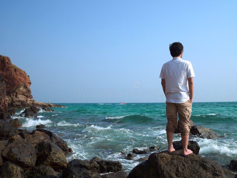 Achtermening van de eenzame Aziatische mens die zich op de steen van overzeese kust bevinden en ver weg bekijken bij stock foto's