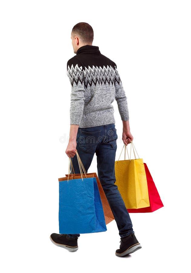 Achtermening van de gaande mens met het winkelen zakken royalty-vrije stock fotografie