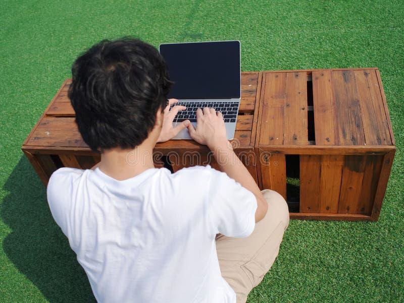 Achtermening van de jonge Aziatische mens die computerlaptop in openlucht met behulp van bij stock afbeeldingen
