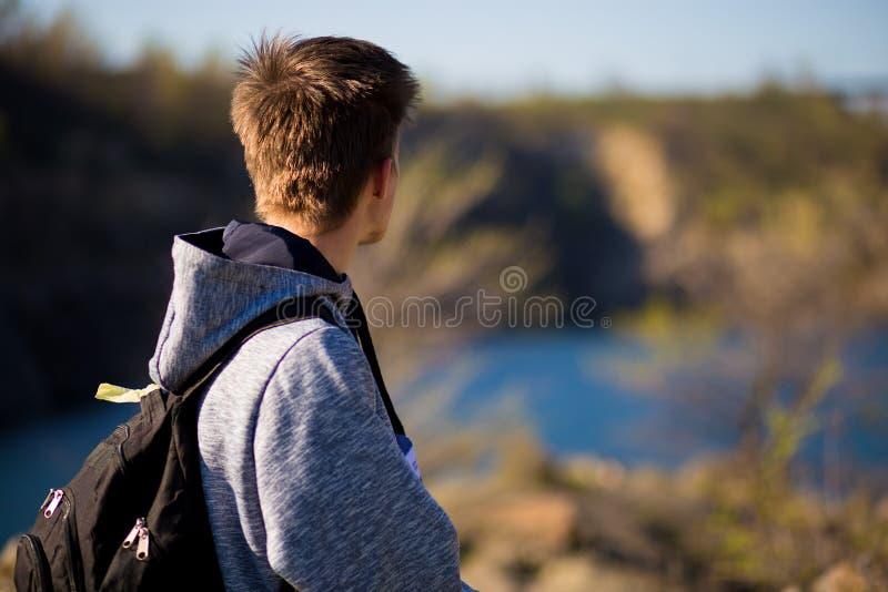 Achtermening van de jonge mens die de mooie mening bij het meer bekijkt Reis en psychologieconcept royalty-vrije stock fotografie