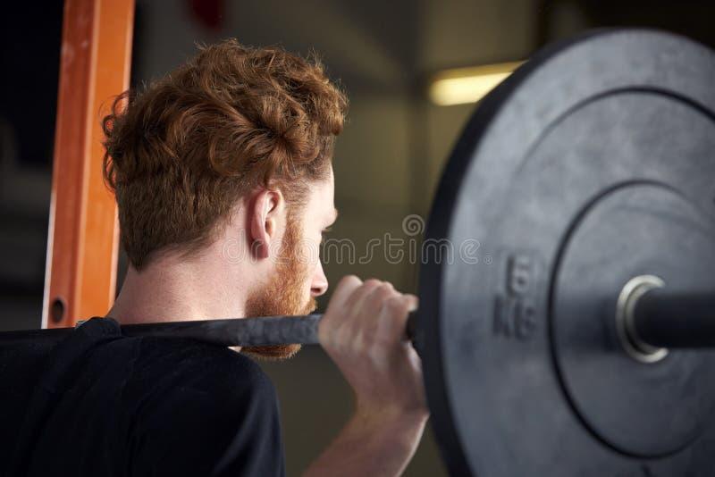 Achtermening van de Jonge Mens in Gymnastiek het Opheffen Gewichten op Barbell stock afbeelding