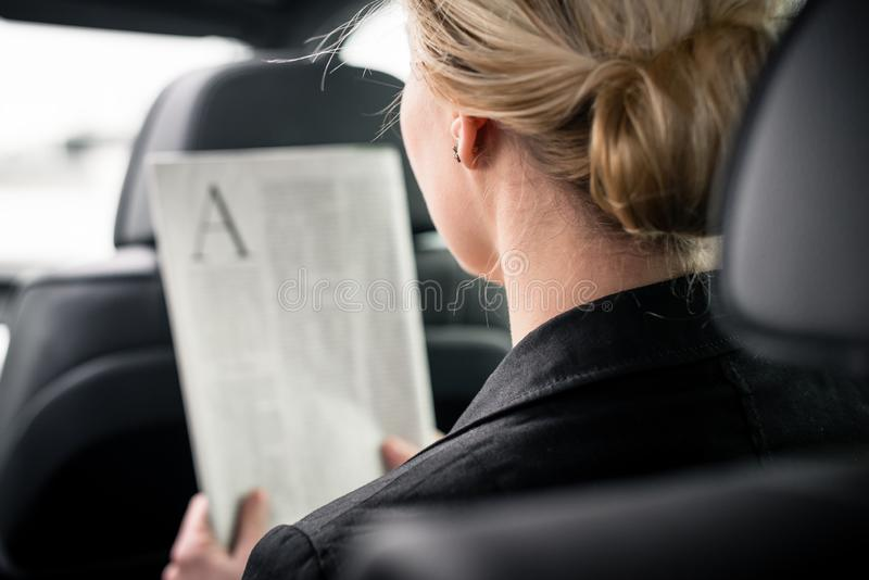 Achtermening van de krant van de onderneemsterlezing in auto royalty-vrije stock foto