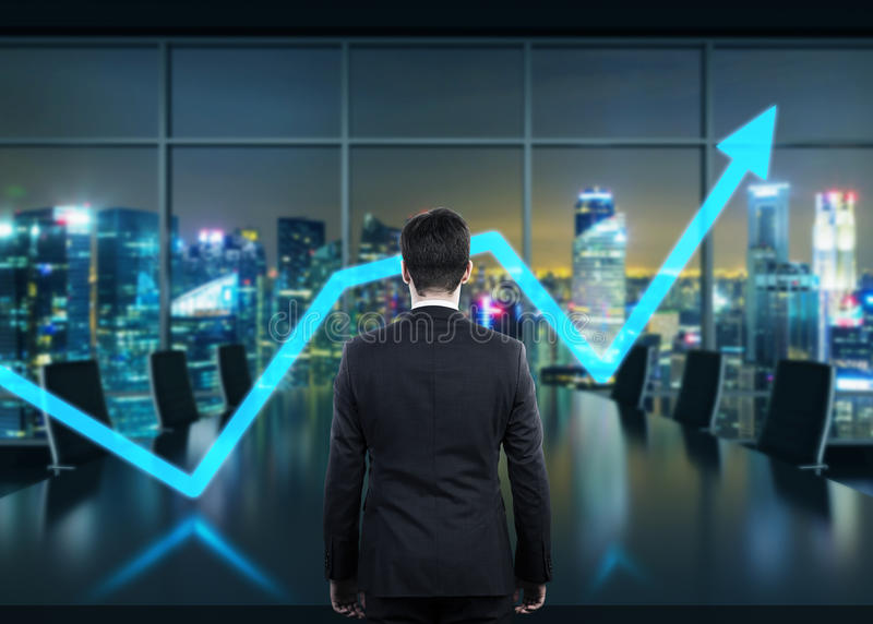 Achtermening van de man in het bureau bij nacht Het toenemen pijl als symbool van het succes royalty-vrije stock afbeelding
