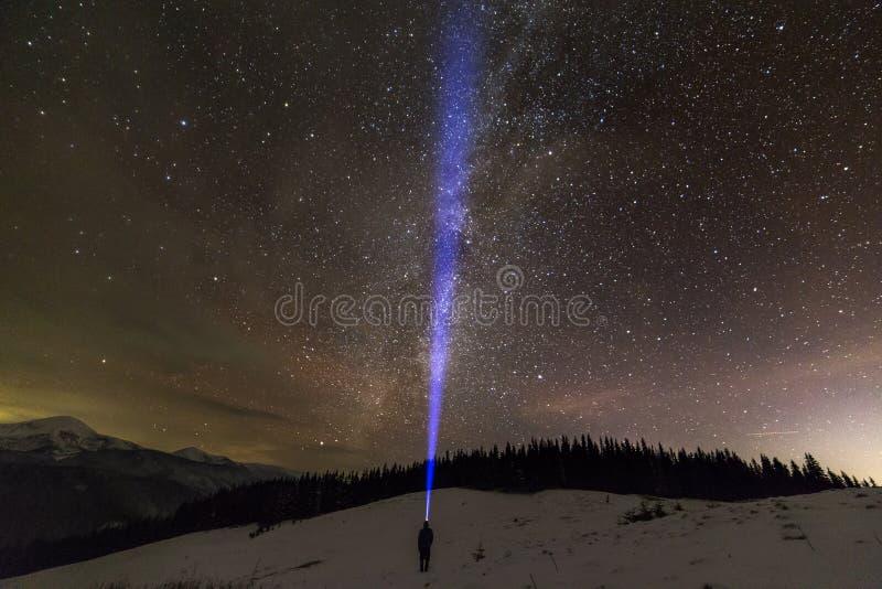 Achtermening van de mens met hoofdflitslicht die op sneeuwvallei onder mooie donkerblauwe de winter sterrige hemel zich bevinden, stock foto's