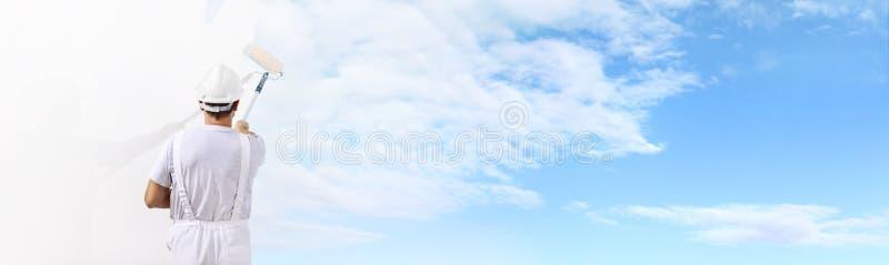 Achtermening van de schildersmens die de blauwe hemel op blinde muur schilderen stock afbeelding