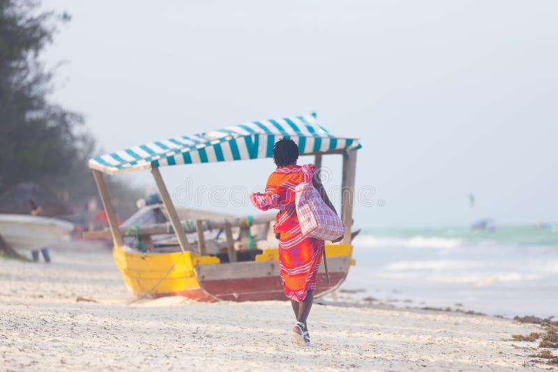 Achtermening van de traditonaly geklede verkopende hand van de maasaimens - gemaakte juwelen op strand van beeld het perfecte tro royalty-vrije stock fotografie
